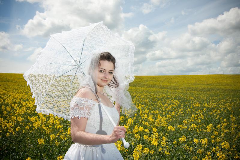 Mariée avec son umbrelle dans un champs de colza